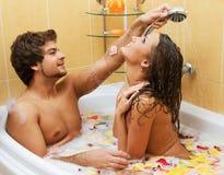 享用年轻人的浴美好的夫妇 免版税库存图片