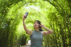 享用年轻人相当中国亚裔的妇女获得拍与手机照相机摆在的乐趣selfie照片凉快 库存照片