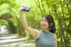 享用年轻人相当中国亚裔的妇女获得拍与手机照相机摆在的乐趣selfie照片凉快 库存图片