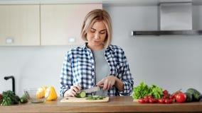 享用年轻微笑的偶然的妇女烹调砍黄瓜的沙拉使用刀子 影视素材