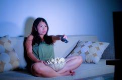享用年轻甜和愉快的亚裔韩国的妇女生活方式画象看电视使用遥控吃玉米花la 免版税库存图片