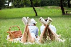 享用年轻的夫妇放松野餐时间在公园,说谎在野餐毯子 免版税库存照片