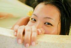 享用年轻美丽和愉快的轻松的亚裔的韩国女人沉溺在浴缸的牛奶浴在豪华温泉微笑高兴 免版税图库摄影