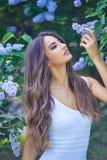 享用开花的丁香的气味年轻美丽的妇女在一个晴天 免版税库存图片