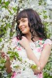享用开花的树的气味在晴朗的年轻美丽的妇女 免版税库存图片