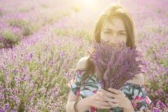 享用开花的淡紫色花束的愉快的妇女 库存照片