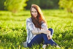 享用开花的蒲公英的气味年轻美丽的红头发人妇女在一好日子 接近的眼睛 免版税库存照片