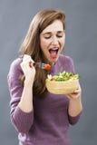 享用微笑的20s的女孩吃乐趣的开胃素食者食物有新饮食 免版税库存照片