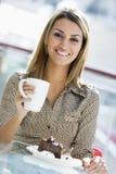 享用快餐妇女的咖啡馆 免版税库存图片