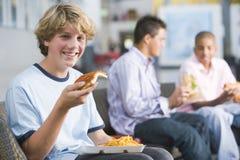 享用快餐的男孩一起吃午餐少年 免版税库存图片