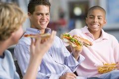 享用快餐的男孩一起吃午餐少年 库存图片