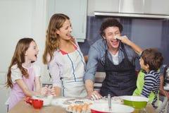 享用愉快的家庭,当烹调食物时 图库摄影
