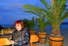 享用手机海滩餐馆的成熟妇女 库存照片