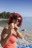 享用新鲜的海鲜三明治的俏丽的妇女 库存图片