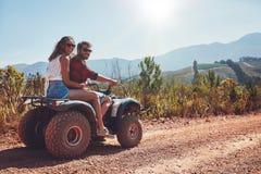 享用方形字体自行车的夫妇在乡下乘坐 免版税库存照片