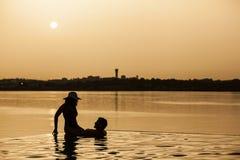 享用旅馆水池的年轻和英俊的夫妇 免版税图库摄影