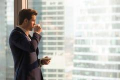 享用早晨咖啡的商人在办公室 免版税库存图片