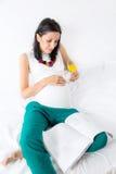 享用早晨杯橙汁的孕妇在床上 库存照片