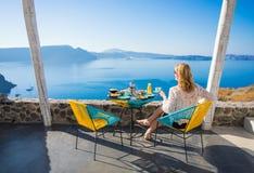 享用早餐有从大阳台的美丽的景色的妇女 图库摄影