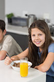 享用早餐的两微笑的兄弟姐妹画象  库存图片