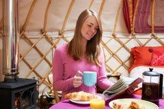 享用早餐的妇女,野营在传统Yurt 图库摄影