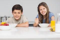 享用早餐的微笑的年轻兄弟姐妹在厨房里 图库摄影