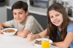 享用早餐的微笑的年轻兄弟姐妹在厨房里 免版税库存图片