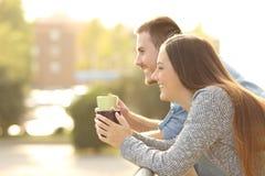 享用早餐的愉快的夫妇在阳台上 免版税库存图片