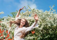 享用春天近的开花的树的女孩 免版税库存图片