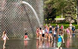 享用普遍的冠喷泉的孩子在千禧公园在一个热的夏日在芝加哥街市 库存图片