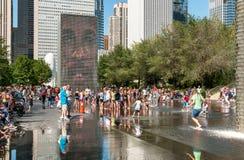 享用普遍的冠喷泉的访客在千禧公园在一个热的夏日在芝加哥街市 免版税库存照片