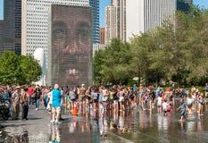享用普遍的冠喷泉的访客在千禧公园在一个热的夏日在芝加哥街市 库存照片