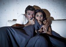 享用有吸引力的夫妇在家观看电视与毯子的恐怖片覆盖物 免版税库存图片