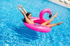 享用有太阳镜的假期女孩在游泳池 库存照片