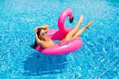享用有太阳镜的假期女孩在游泳池 库存图片