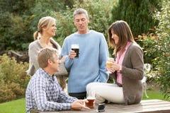 享用朋友的饮料从事园艺户外客栈 免版税库存照片
