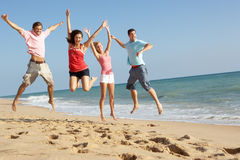 享用朋友组节假日星期日的海滩 免版税库存照片