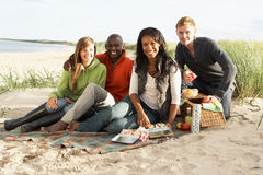享用朋友野餐年轻人的海滩 图库摄影