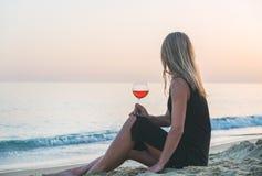 享用杯在海滩的玫瑰酒红色的年轻白肤金发的妇女由海在日落 免版税库存照片