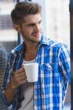 享用杯子咖啡的年轻商人 免版税库存图片