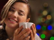 享用杯子热饮料的少妇 免版税图库摄影