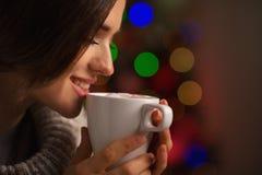享用杯子热饮料的愉快的少妇 免版税库存图片