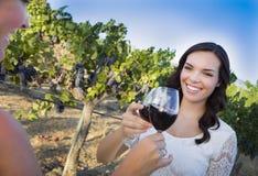 享用杯酒的少妇在有朋友的葡萄园里 免版税图库摄影