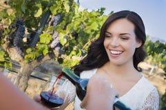 享用杯酒的少妇在有朋友的葡萄园里 免版税库存照片