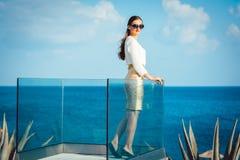 享用杯香槟的妇女在海 免版税库存图片