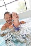 享用极可意浴缸的微笑的夫妇 免版税库存照片