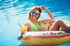 享用比基尼泳装的晒黑妇女在游泳池的可膨胀的床垫 免版税库存图片