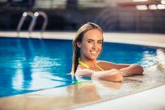 享用比基尼泳装的晒黑妇女在游泳池 库存照片