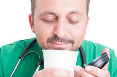 享用气味或新鲜的咖啡的医生 免版税库存照片