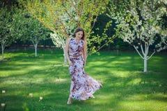 享用气味的画象美丽的愉快的妇女在一个开花的春天开花的庭院里 在blos附近的聪慧和时兴的微笑的女孩 库存图片